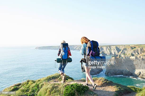 hikers walking along coastal path. - rucksacktourist stock-fotos und bilder