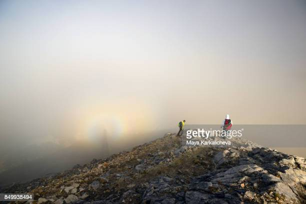 hikers walking in the mist with brocken spectre optical phenomenon - light natural phenomenon stock pictures, royalty-free photos & images