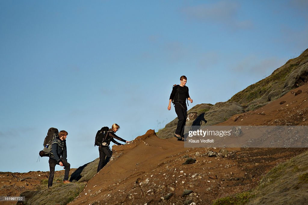 3 hikers walking on mountain side : Stock Photo