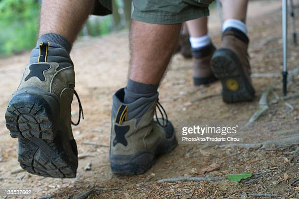 hikers walking on path, close-up of feet - human foot stock photos and pictures