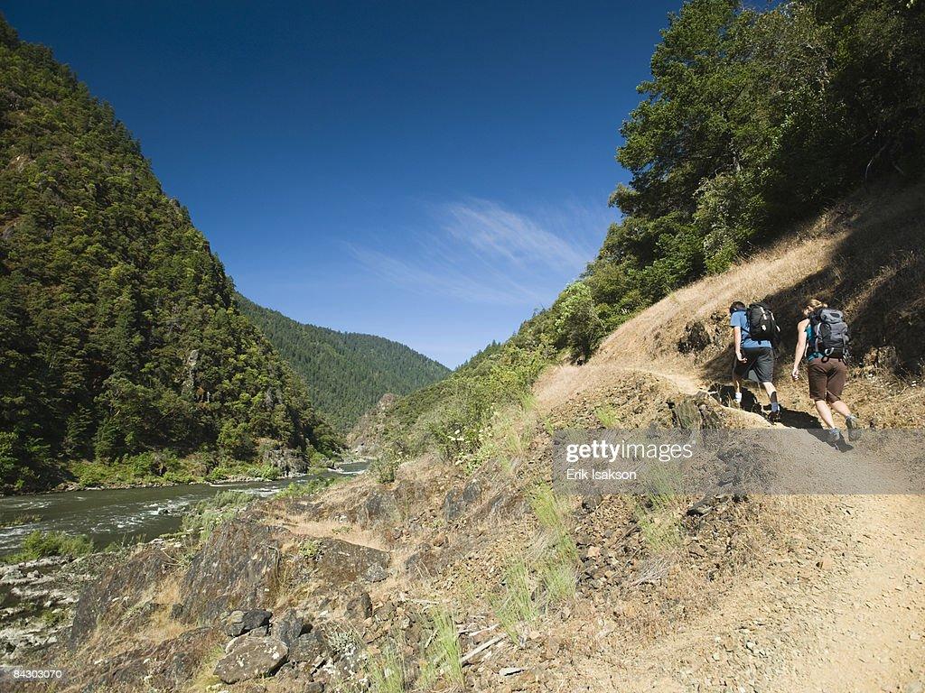 Hikers walking on riverside trail : Stock Photo