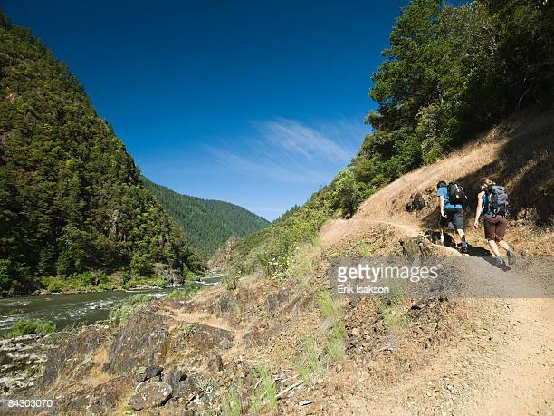 hikers walking on riverside trail - the oregon trail stock photos and pictures