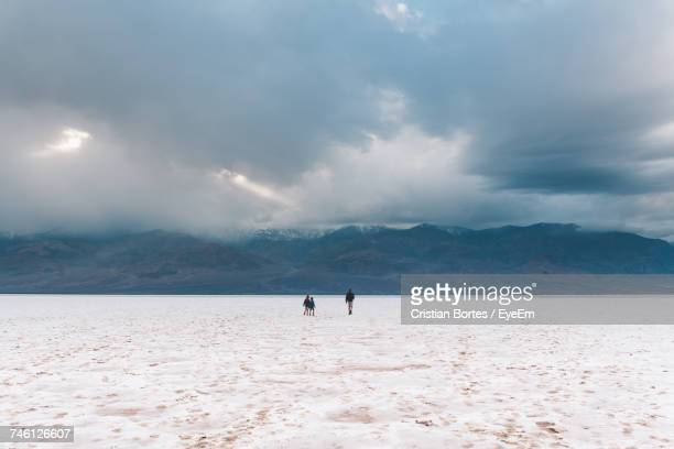 Hikers Walking On Snow Covered Landscape Against Cloudy Sky