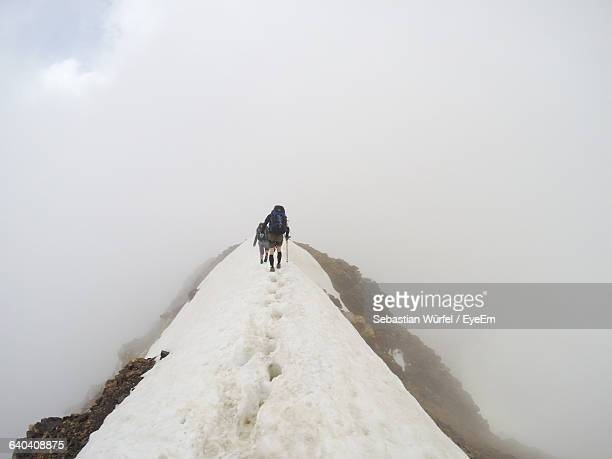 Hikers Walking On Snow Covered Mountain Against Sky