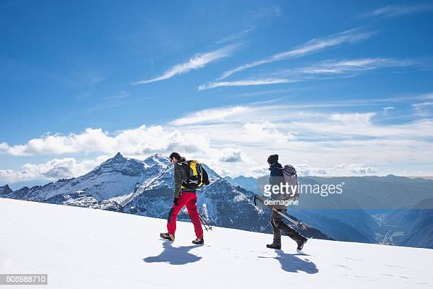 Hikers walking on snow-covered field at high altitude