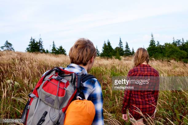 Hikers Walking Through Field
