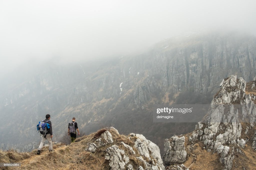Hikers walking to mountains range : Stock Photo