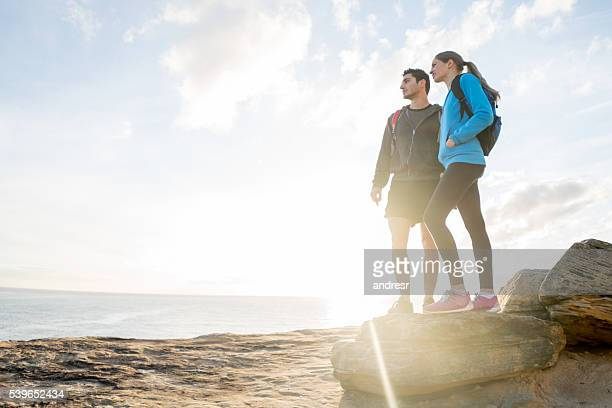 Hikers watching the sunset at the beach