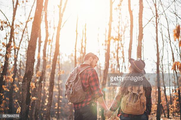 Hikers with backpacks walking in forest