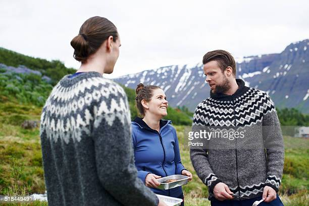Hikers with food standing against mountains