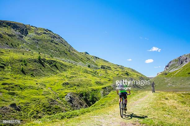 Hikers with mountain bike in a mountain valley