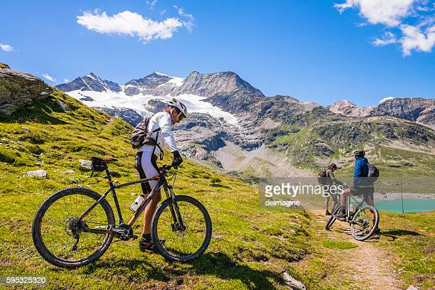 hikers with mountain bike in a mountain valley - bicycle trail outdoor sports stock photos and pictures