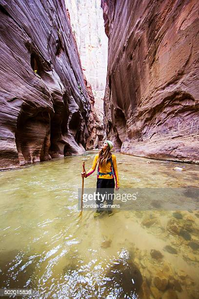 hiking a slot canyon filled with water. - utah stock pictures, royalty-free photos & images