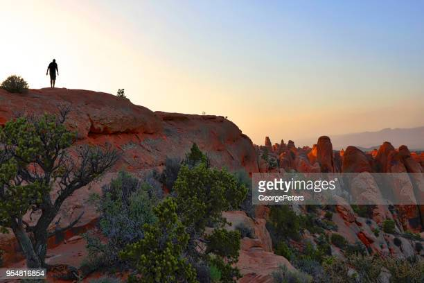 Hiking across rock fin in Arches National Park. Double O Arch Trail.