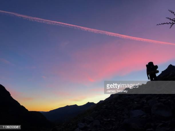 hiking at a pink and yellow sunrise in patagonia - calm before the storm stock pictures, royalty-free photos & images