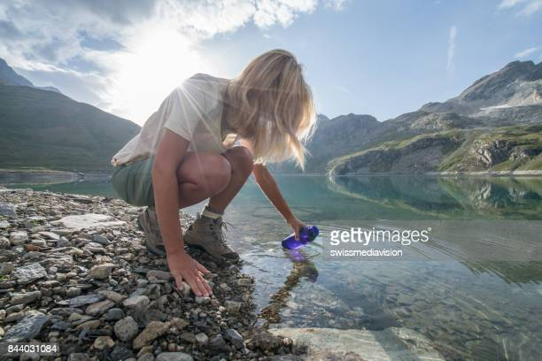 Hiking blond girl filling bottle from mountain lake