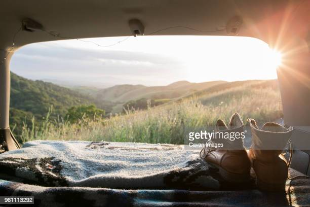 hiking boots and blanket in sports utility vehicle with hills in background - car trunk stock pictures, royalty-free photos & images