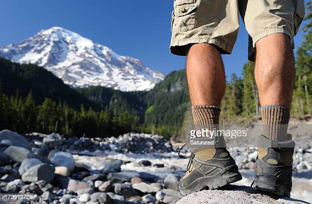 Hiking Boots and Legs of a Man Overlooking Mountain