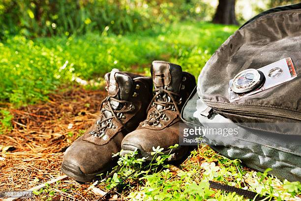 Hiking boots, backpack, compass, next to woodland path