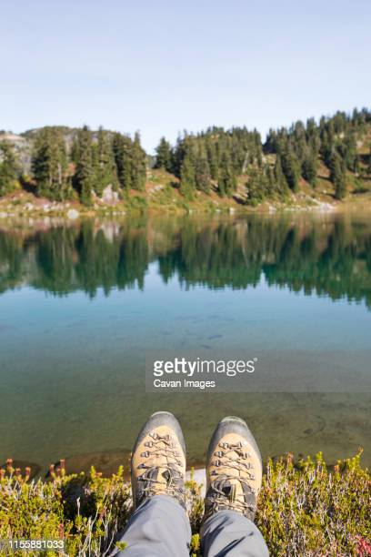Hiking boots in front of tranquil alpine tarn, B.C., Canada.