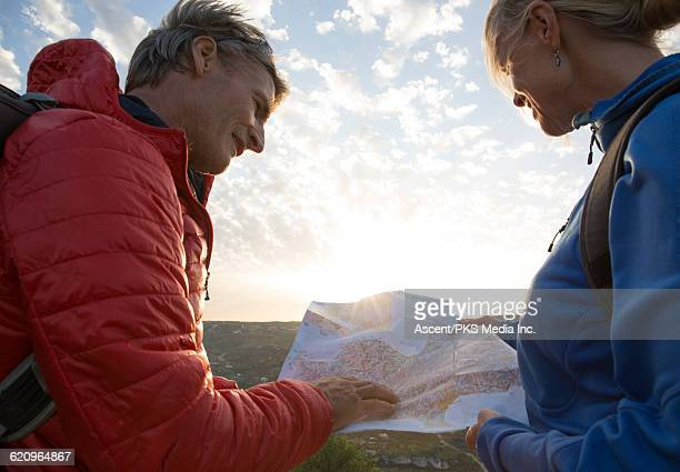hiking couple consult map for direction, hilltop - 50 59 years stock pictures, royalty-free photos & images