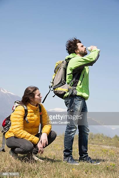Hiking couple drinking water bottle, Vogogna, Verbania, Piemonte, Italy