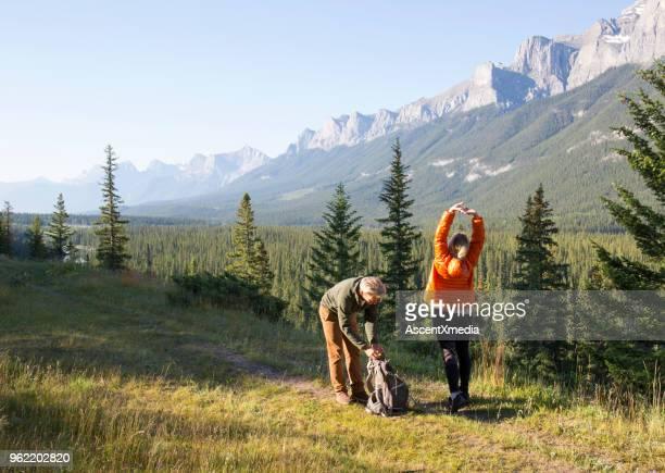 Hiking couple follow trail through mountain meadow