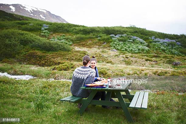 Hiking couple having food at table on mountain