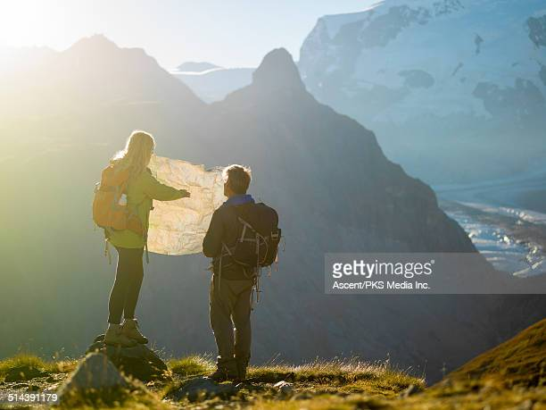 Hiking couple look at map in mountain meadow