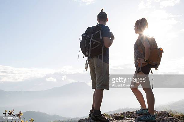 Hiking couple look out across hilly landscape