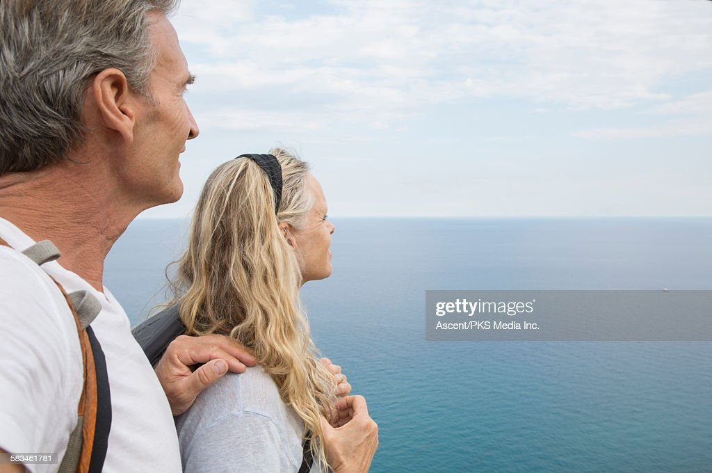 Hiking couple look out across sea, from above : Stock Photo