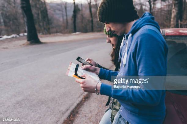hiking couple looking at map and smartphone on forest roadside, monte san primo, italy - chum stock-fotos und bilder