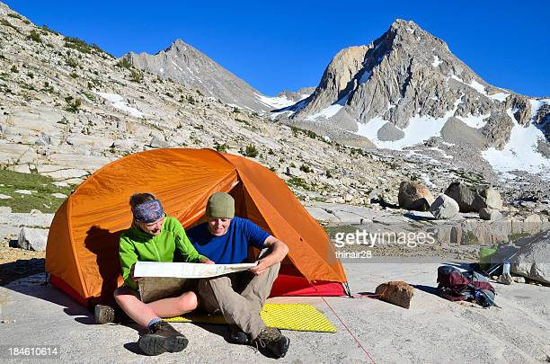 hiking couple looking at map - john muir trail stock photos and pictures