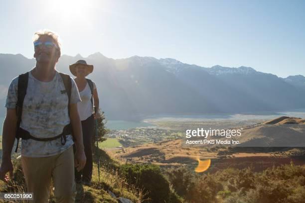 Hiking couple pause on mountain ridge, looking off