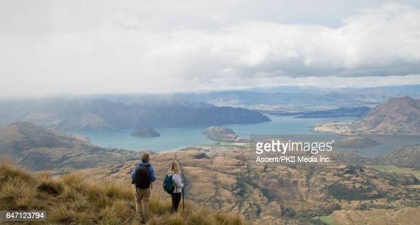 Hiking couple pause on mountain slope, look out to valley
