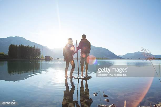 Hiking couple pause on rock island, mtn lake