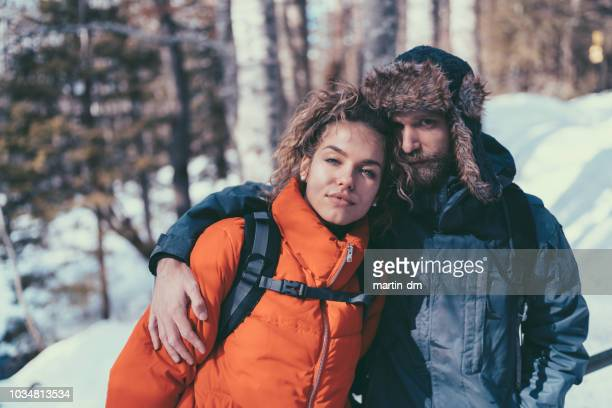 hiking couple portrait - fur hat stock photos and pictures