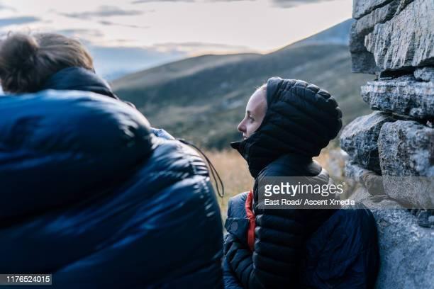 hiking couple relax beside stone hut, in sleeping bags - coat stock-fotos und bilder