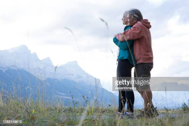 hiking couple relax in grassy meadow in the morning - early retirement stock pictures, royalty-free photos & images