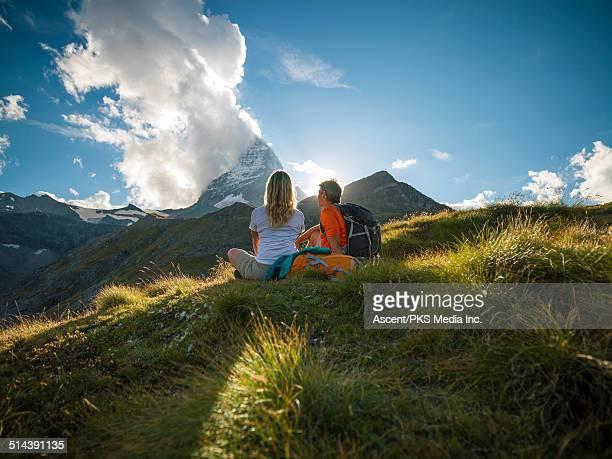 Hiking couple relax in mtn meadow below Matterhorn