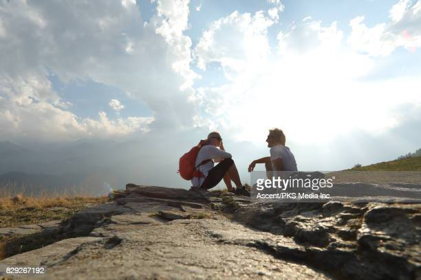 hiking couple relax on rock slabs, mountain meadow - cropped trousers stock pictures, royalty-free photos & images