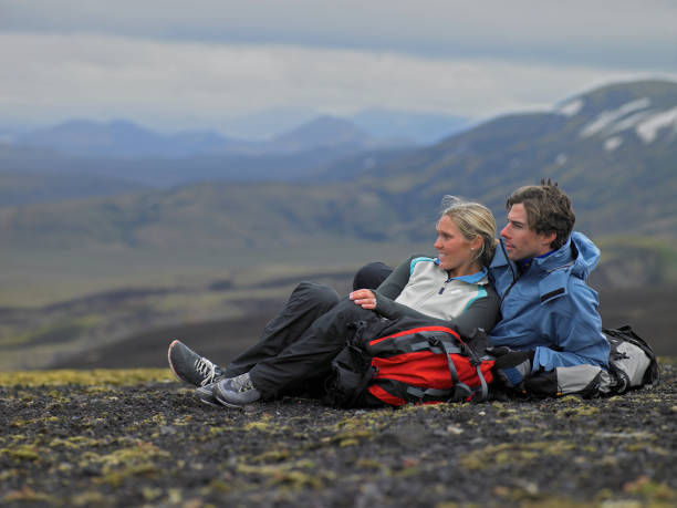 Hiking couple relaxing on mountainside in Iceland