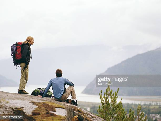 Hiking couple resting on rock overlooking town, rear view