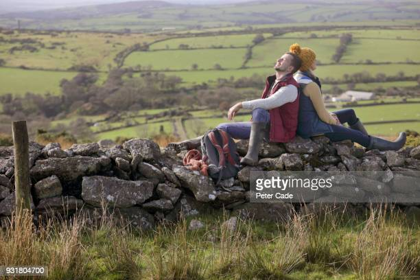 Hiking couple resting on stone wall
