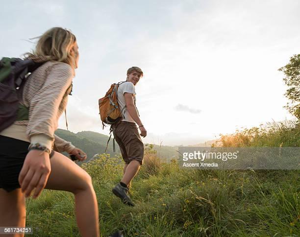Hiking couple set off across hillside meadow