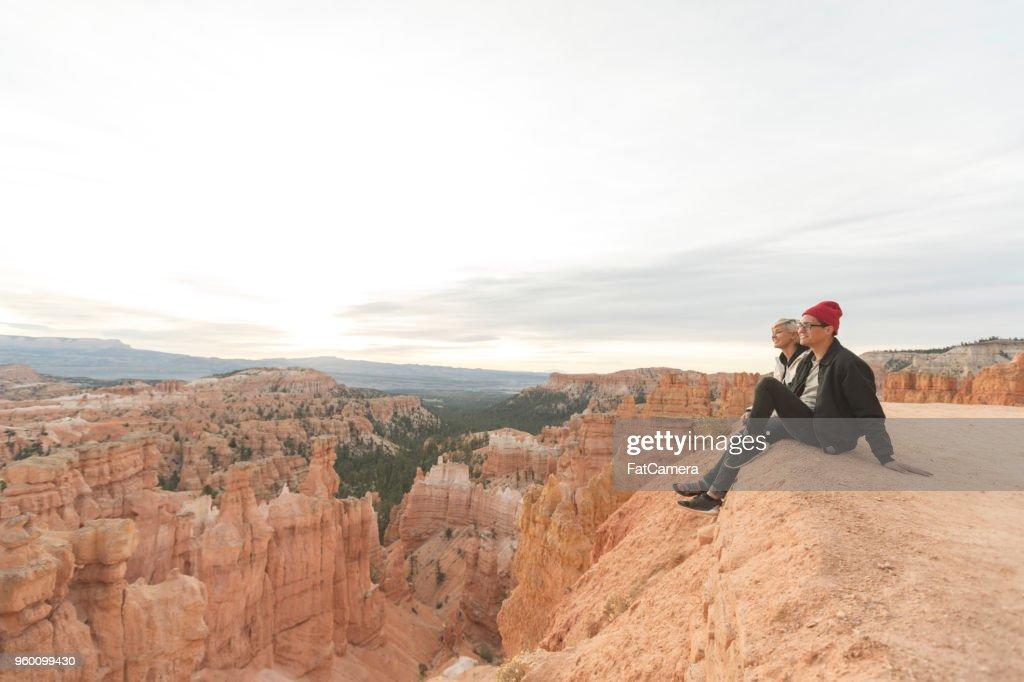 Ein paar Wanderungen am Rand einer Klippe zusammen sitzen und genießen Sie die herrliche Aussicht : Stock-Foto