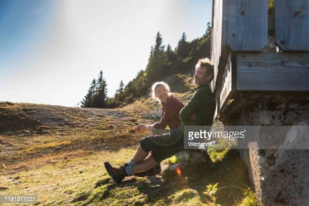 hiking couple sitting in front of mountain hut, taking a break - shack stock pictures, royalty-free photos & images