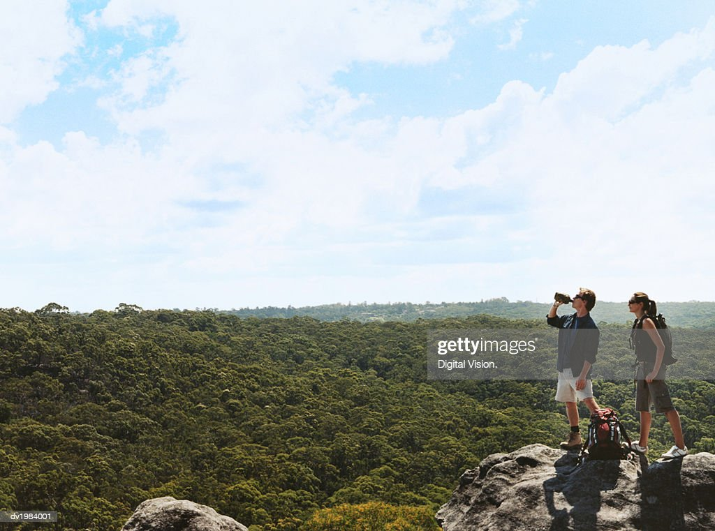 Hiking Couple Stand on a Rock Looking at the View of the Countryside : Stock Photo