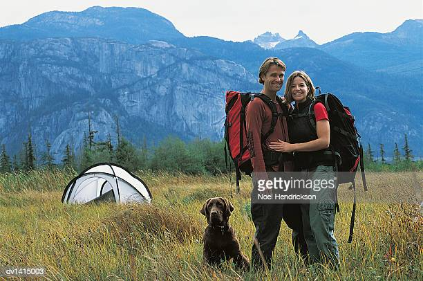 hiking couple standing with dog in front of mountain range and next to tent - next to stock pictures, royalty-free photos & images