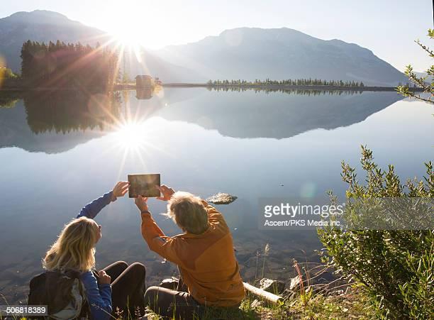 Hiking couple take digital tablet photo, sunrise